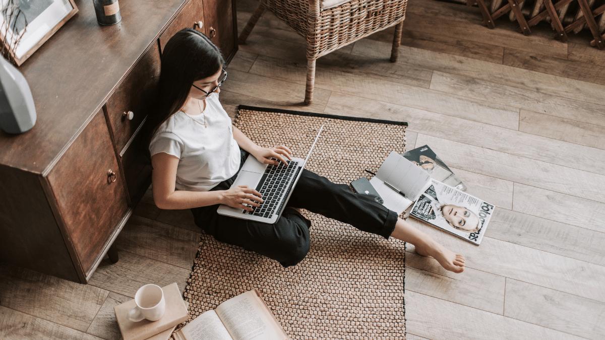 Woman sitting on floor working on laptop